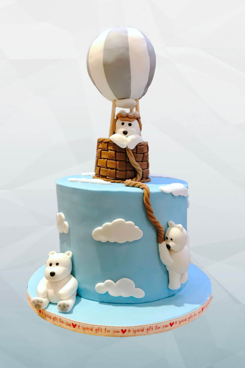 A fondant cake featuring a group of white bears in a hot air balloon