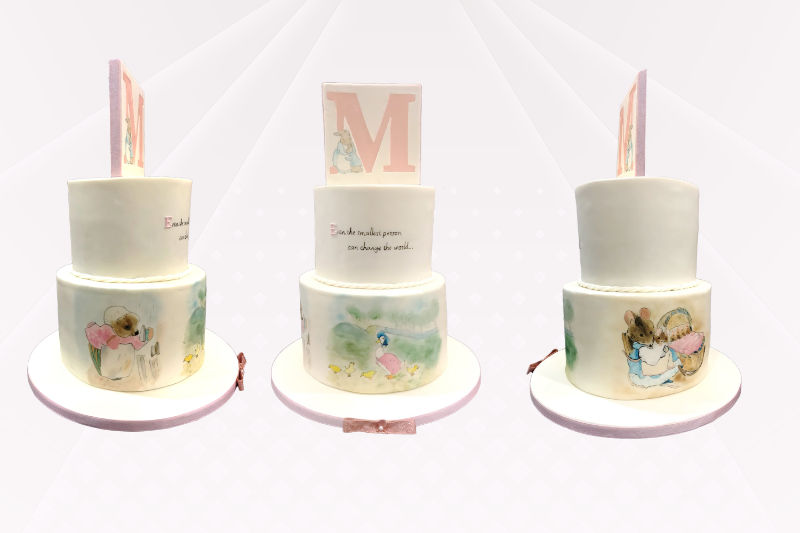 A two tier christening cake decorated with hand-painted characters from Beatrix Potter