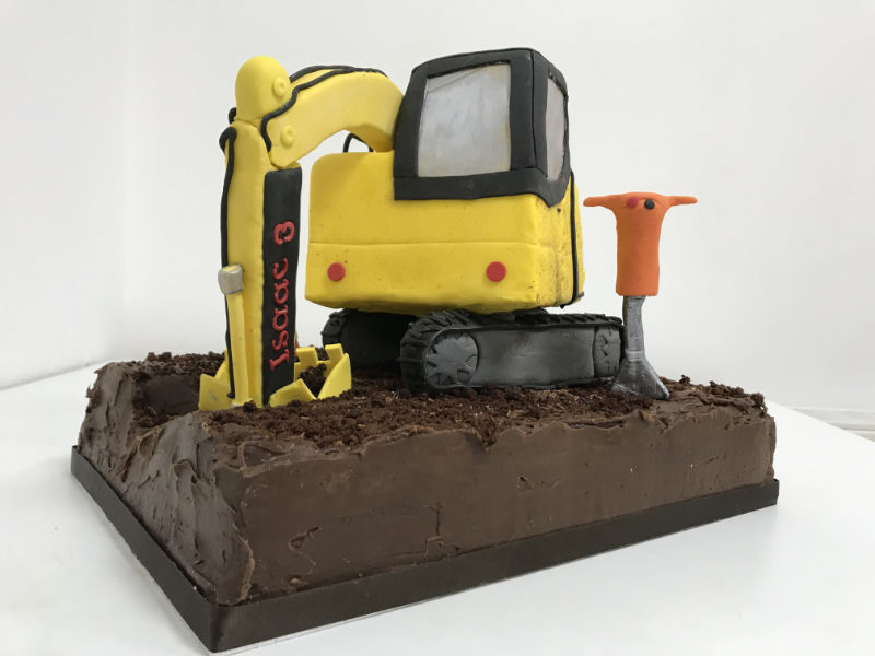 A yellow digger shaped birthday cake
