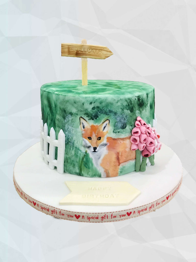 A round cake featuring a hand-painted fox and fondant flowers