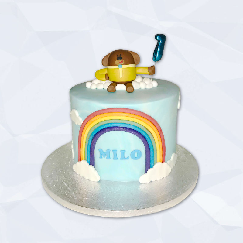 A simple cake featuring the character Hey Duggee, clouds and a rainbow