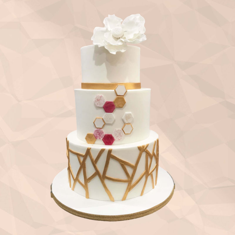 A modern 3-tier wedding cake featuring gold geometric stripes and marble effect tiles