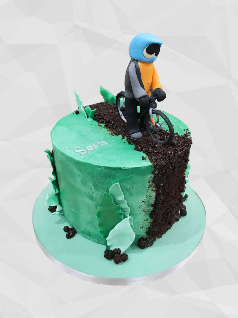 A green cake with a fondant motorbike and motorcyclist placed on top.