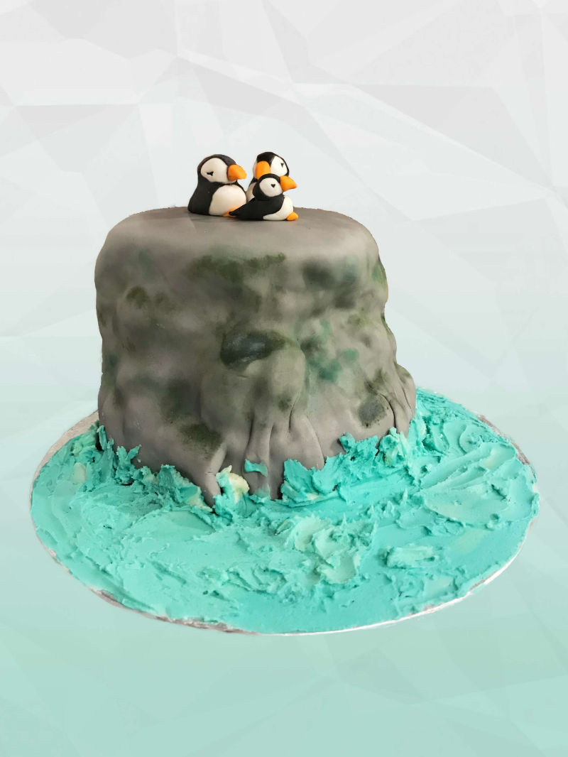 A cake shaped like a large grey rock with a group of penguins huddled on-top. The rock is surrounded by a sea of blue-tinted buttercream