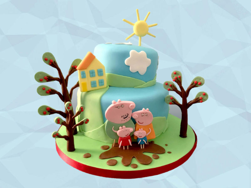A two-tier birthday cake featuring the Peppa Pig family, 3D trees, clouds and a sun.