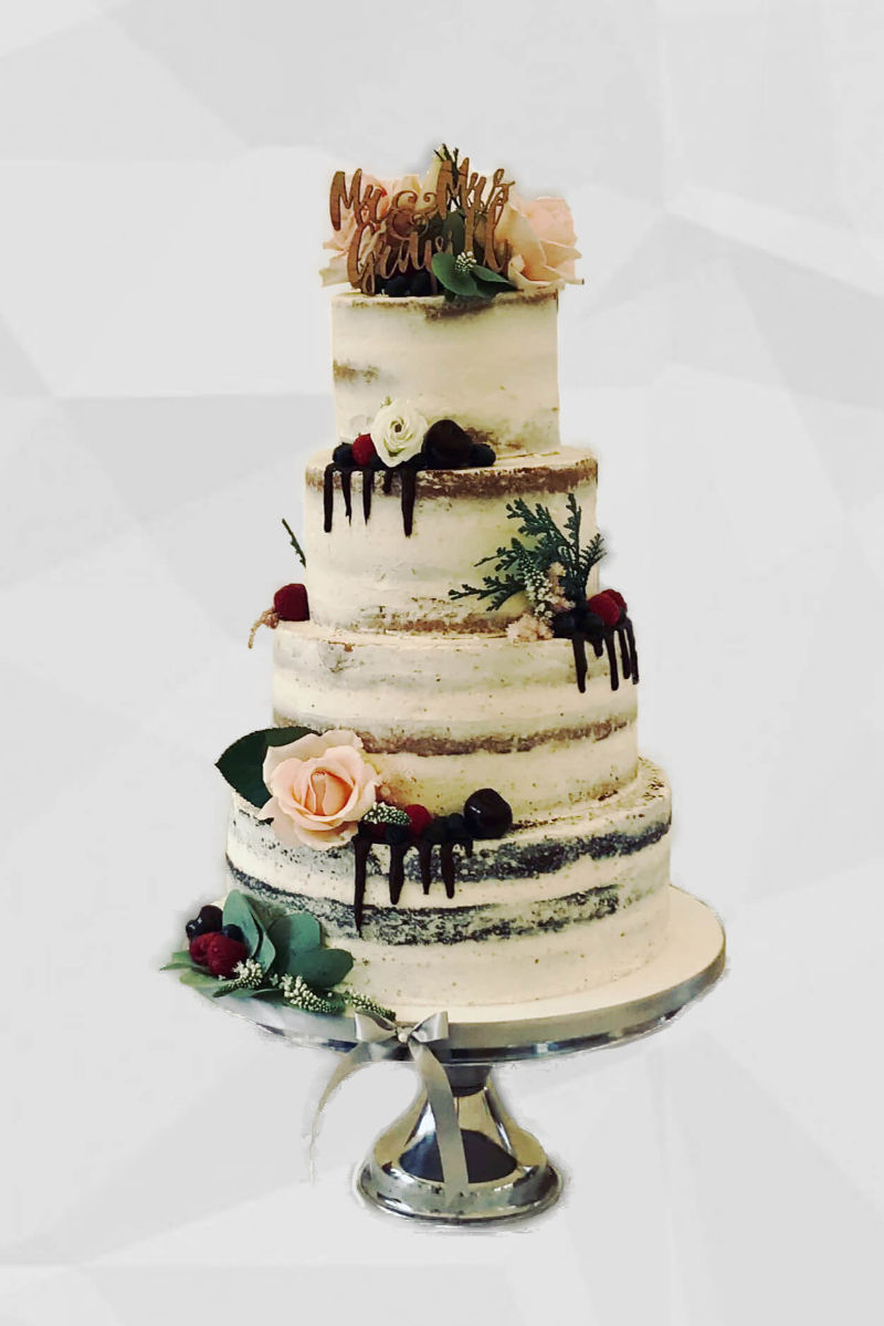A four tier semi-naked buttercream wedding cake decorated with flowers, fruit and dark chocolate