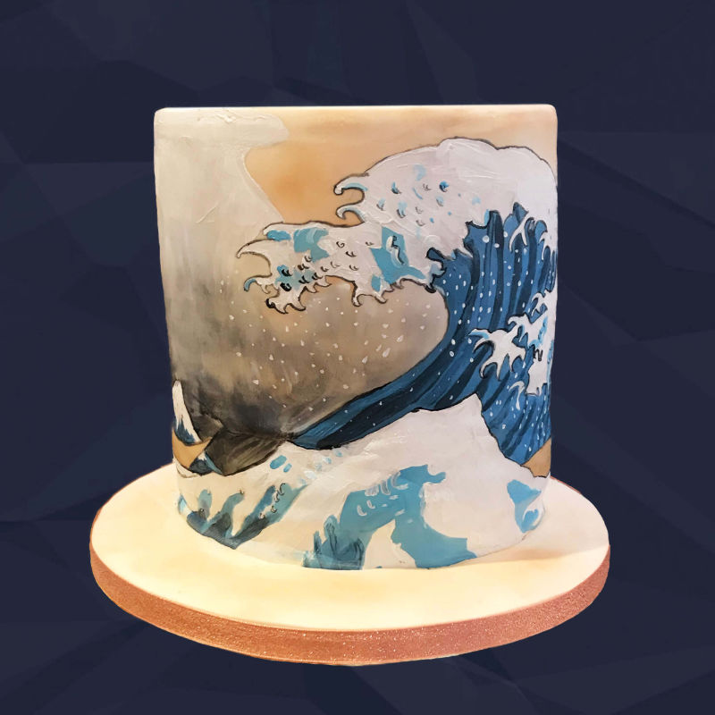 A tall round cake with Hokusai's famous wave painted on around the circumference