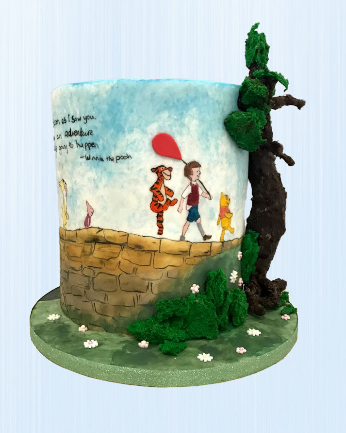 A tall single tier cake decorated with handpainted characters from Winnie the Pooh