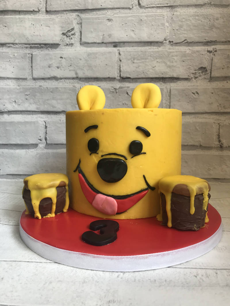 A fondant covered Winnie the Pooh shaped cake