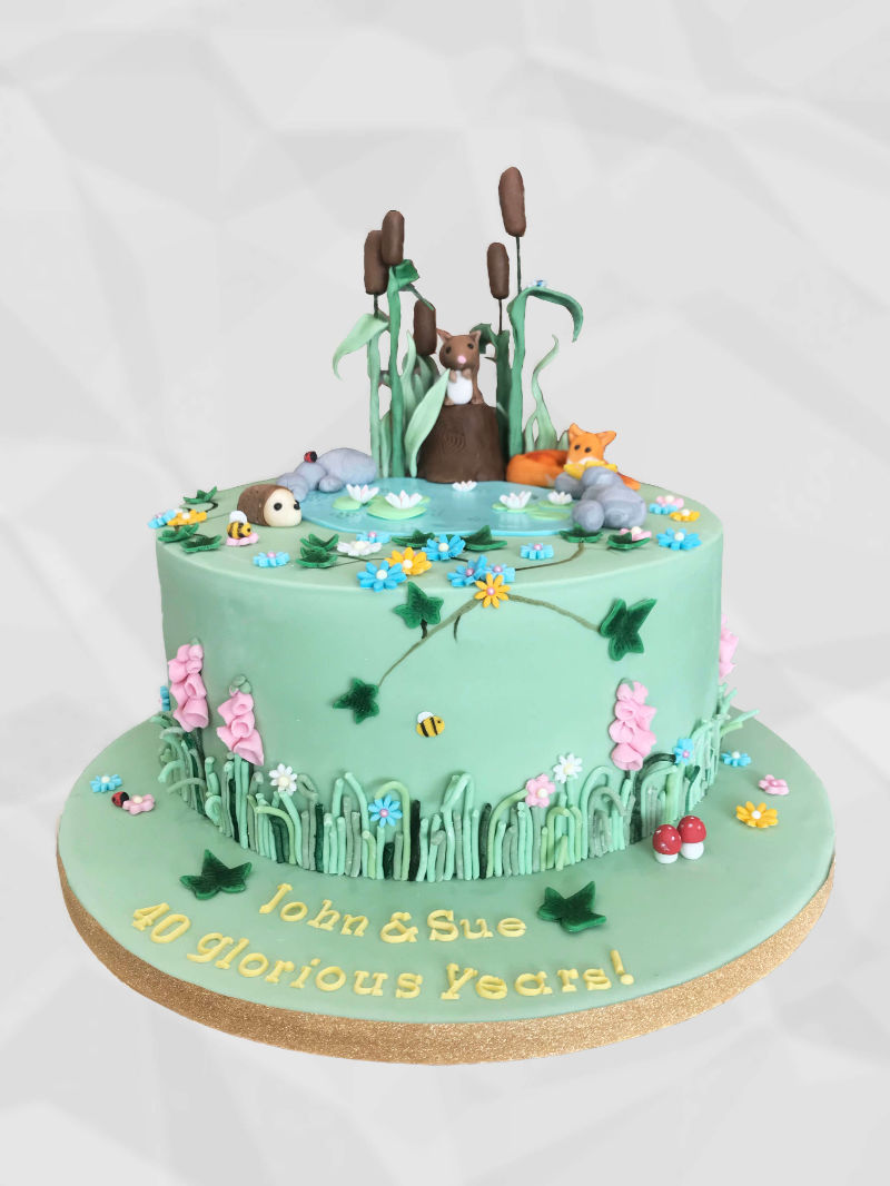 A round cake decorated with mini fondant woodland animals gathered around a pond with mini flowers, rocks and toadstools and ivy. Animals include a squirrel, a fox and a hedgehog
